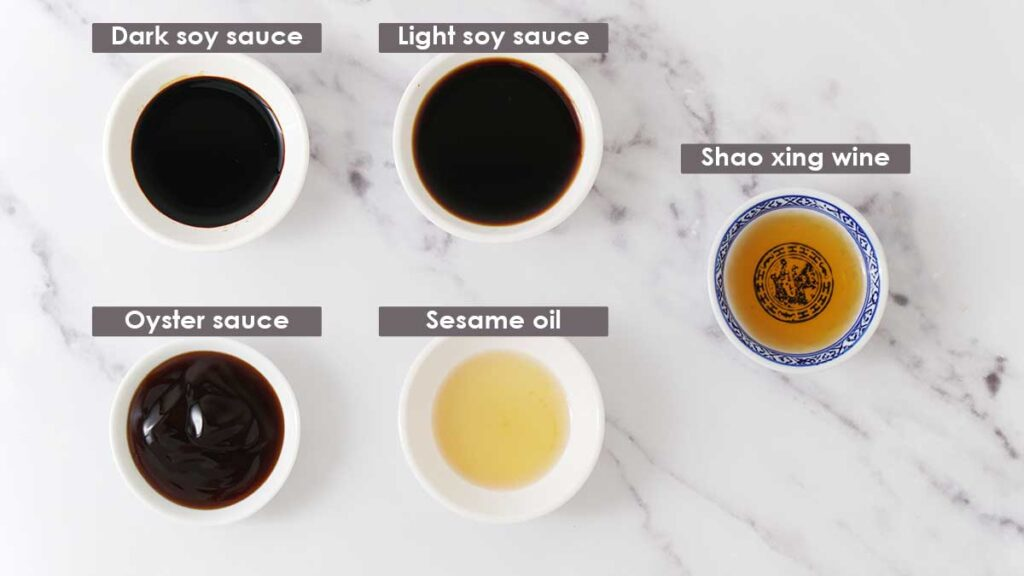 Labelled 5 different types of sauces in small white dipping bowl on the white surface.