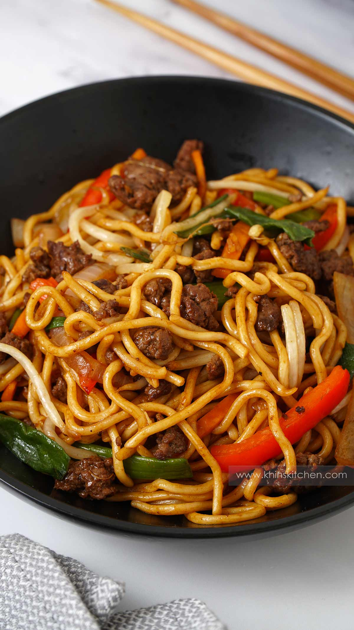 A black bowl containing stir fry noodles, sliced vegetables, ground beef.