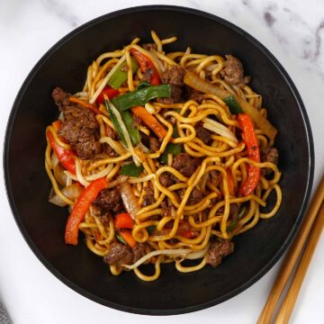A black bowl containing stir fry noodles, ground beef, vegetables and beansprouts.