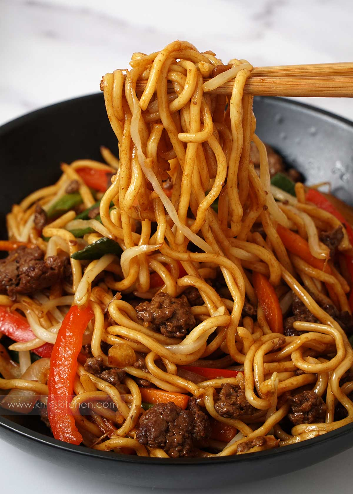 Picking up stir fry noodles with chopstick from the black bowl.
