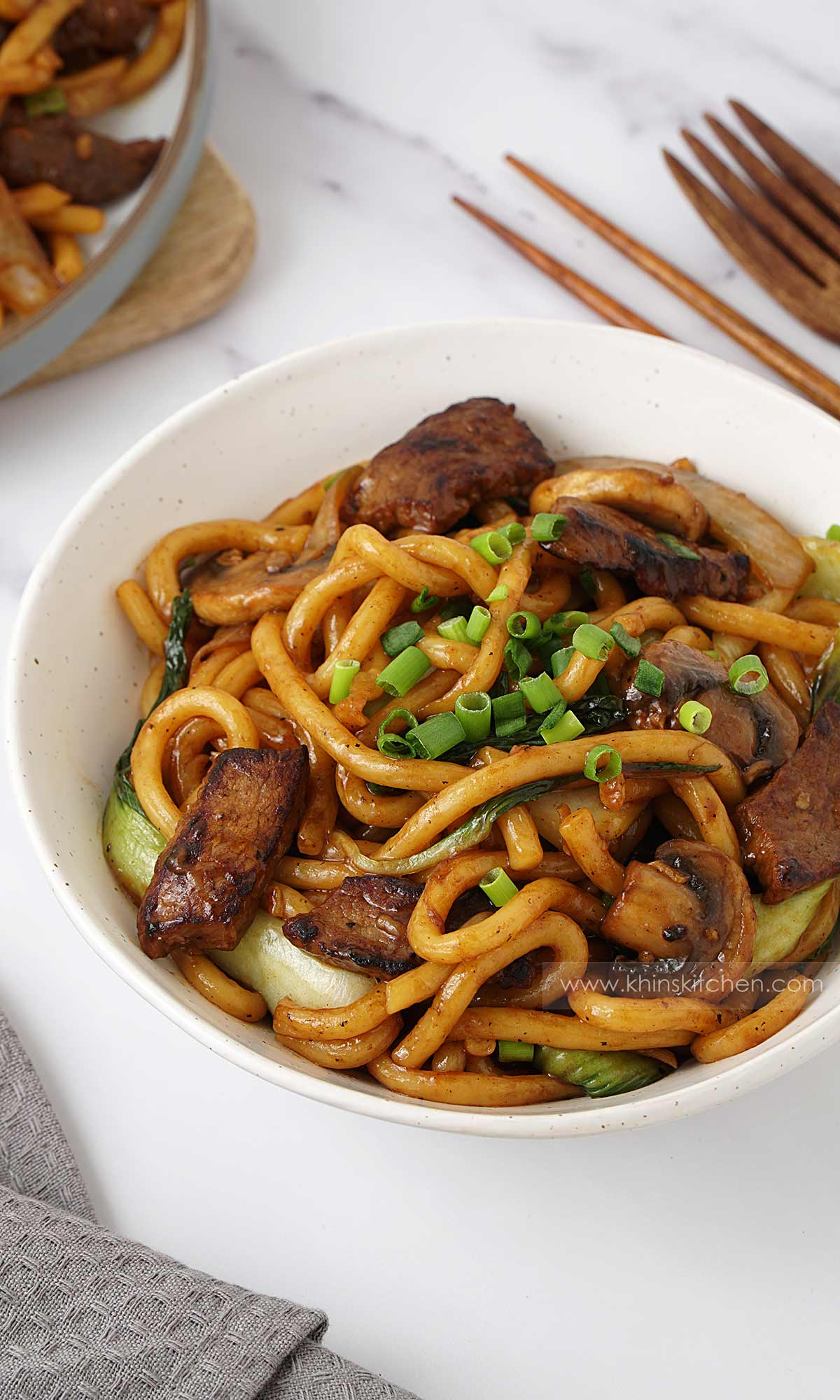 A white bowl containing stir fry udon noodles, with beef slices and vegetables. Topped with chopped spring onions.