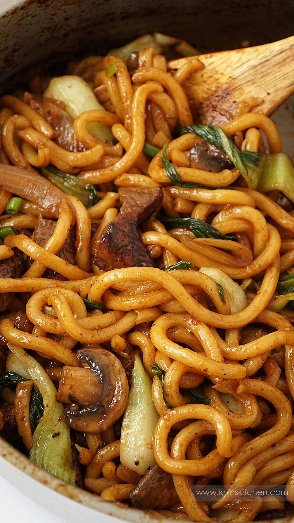 A pan containing stir fry beef, udon noodles, mushroom, green vegetables, and wooden spoon in the background.