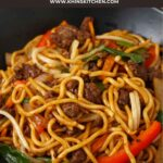 A black bowl containing stir fry noodles, ground beef and vegetables.