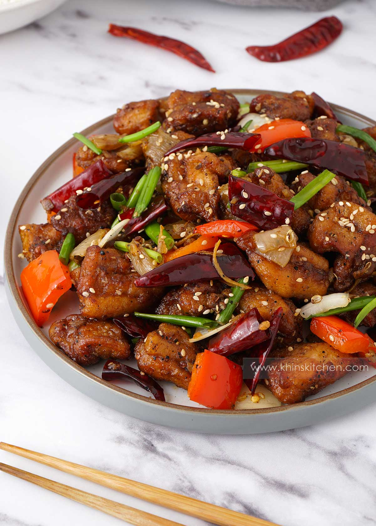 A white plate containing, stir fried chicken, onion, peppers, dry chillies, Sichuan peppercorns and sesame seeds.