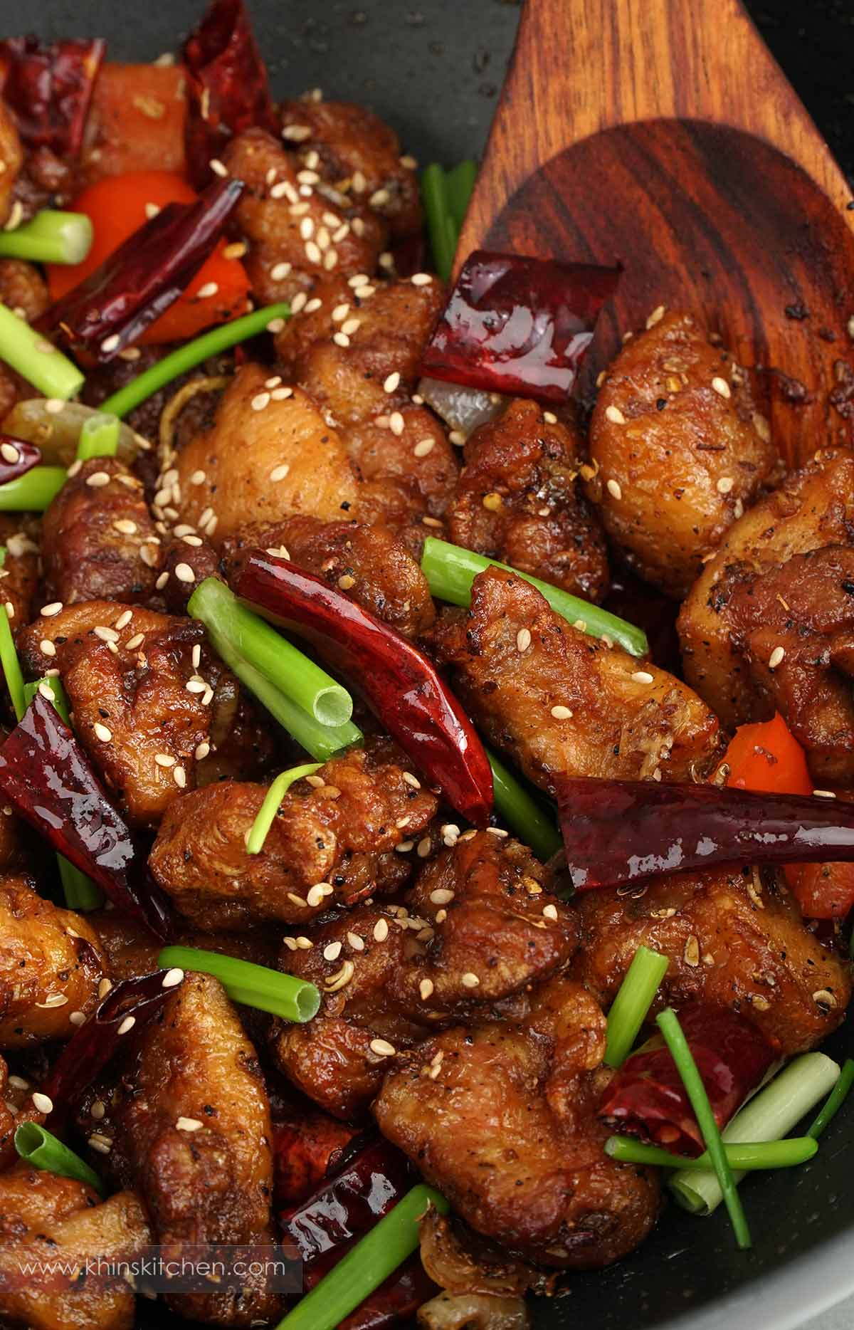 A skillet containing crispy fried chicken, stir fry vegetable and dried red chillies.