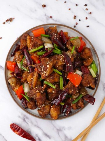 A white plate filled with chinese spicy szechuan chicken and chopstick on the right side of the plate.