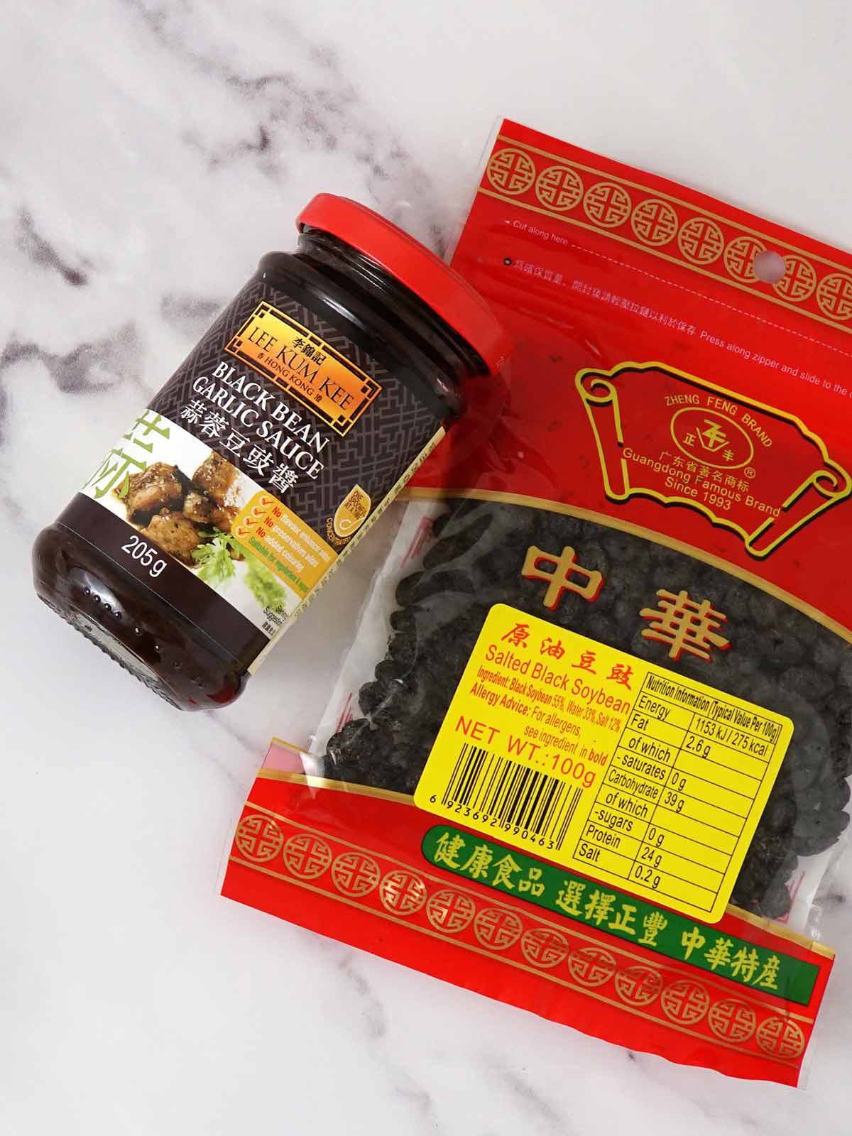 A packet of fermented black soybeans and a jar of black bean garlic sauce displayed on the white table.