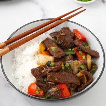 a white bowl containing stir fried beef, stir fried vegetable and sprinkle of spring onions.