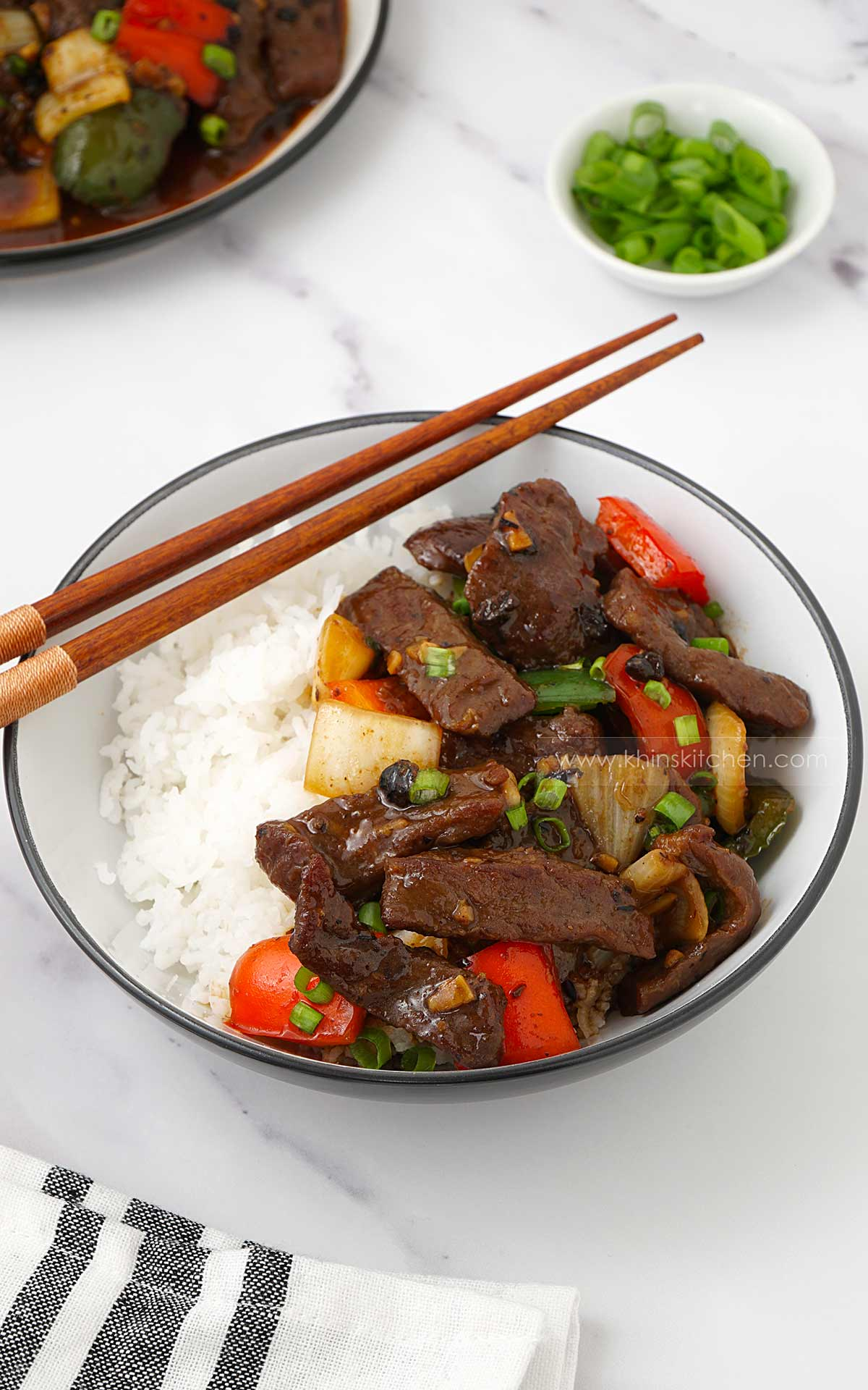 A white bowl containing rice, topped with beef, red peppers, onions and black beans.