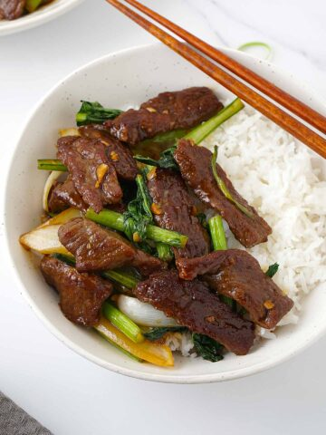 A white bowl containing stir fry beef and green vegetables on top of plain rice.