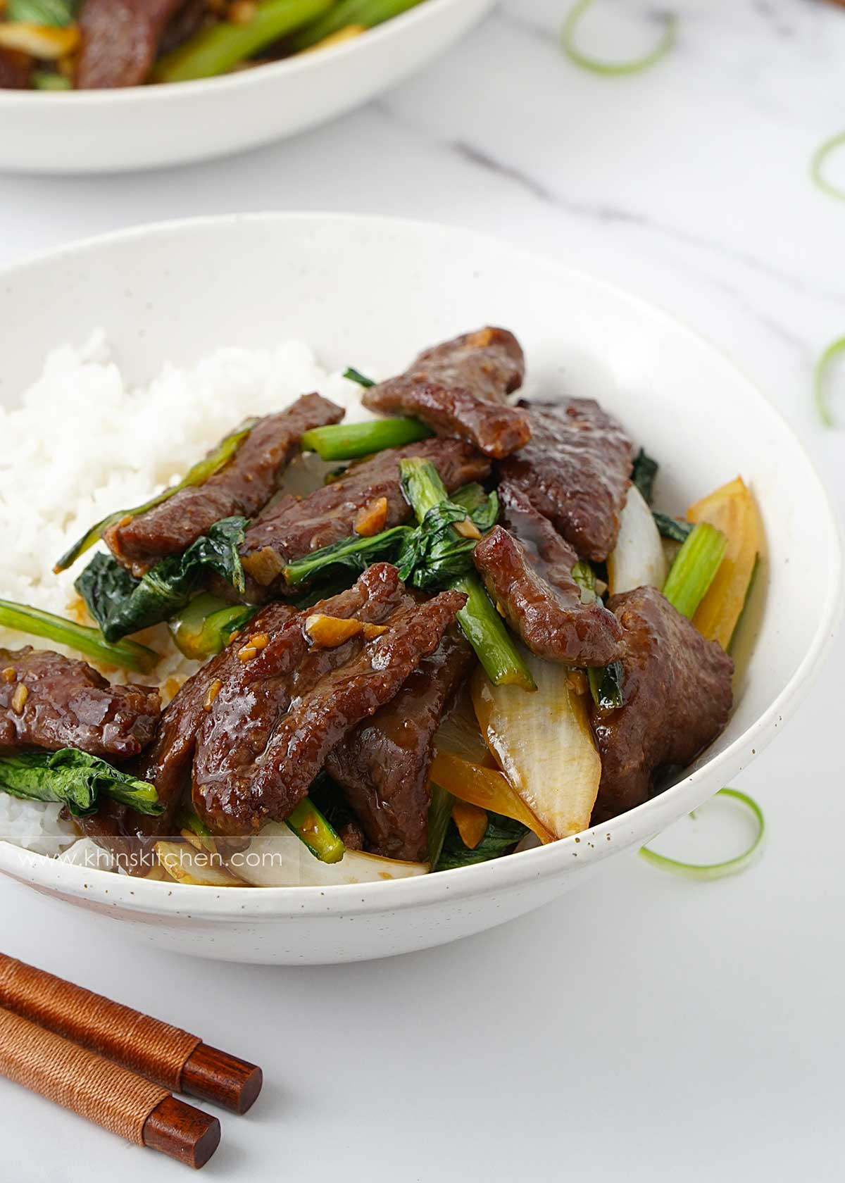 A white bowl containing plain rice, stir fry beef and green vegetables. Wooden chopstick on the left corner.