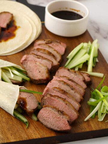 sliced duck, shredded cucumber and shredded spring onions on the wooden serving board and a white small bowl of hoisin dipping sauce.