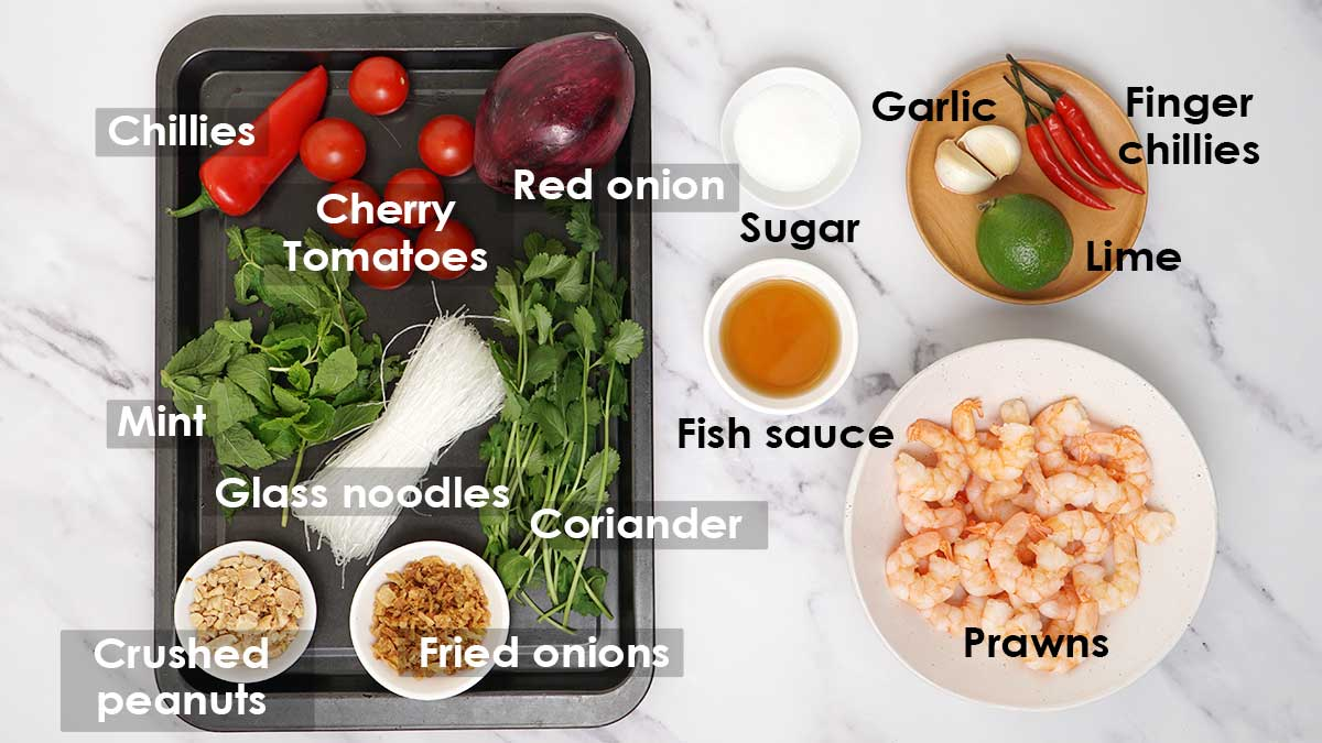 Labelled ingredients of prawn salad and dressing sauce, displayed on the white table.