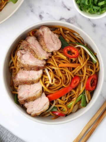 A white bowl filled with stir fry noodles with vegetables topped with sliced roasted duck.