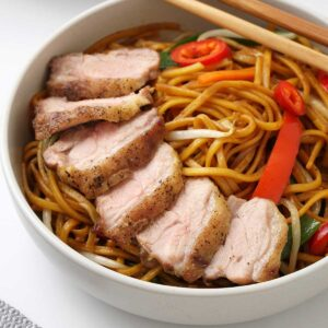 A white bowl containing stir fried noodles topped with roasted sliced duck.