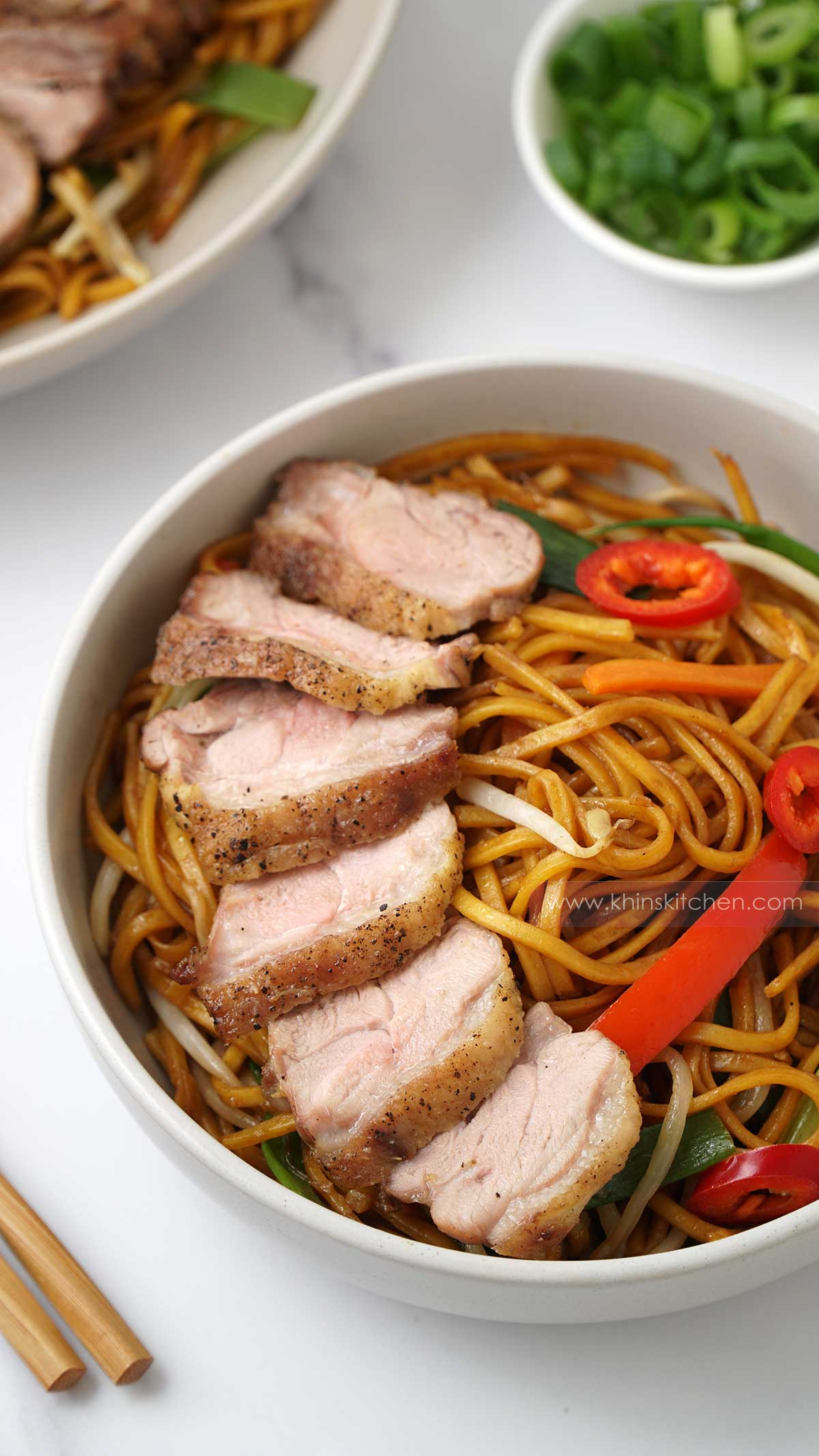 A white bowl containing stir fried noodles, vegetables and roasted sliced duck.