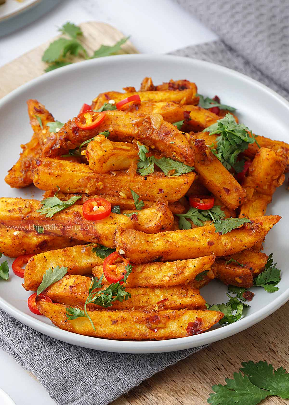 A grey plate containing spicy fried chips topped with sliced chilli and coriander.