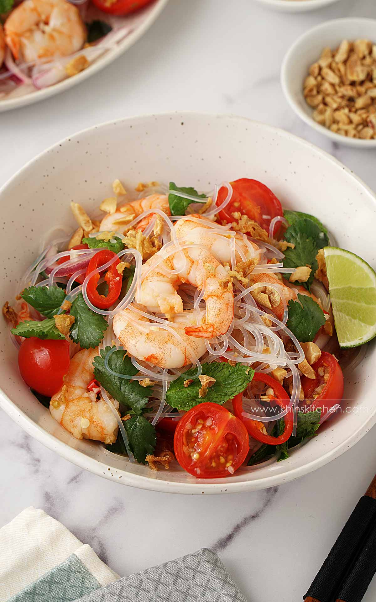 A white bowl containing king prawns, glass noodles, salad vegetables, and lime wedge on the side.