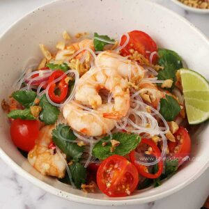A mixture of prawn salad served on the white bowl consisting of cooked prawn, glass noodles, coriander, tomatoes and lime.