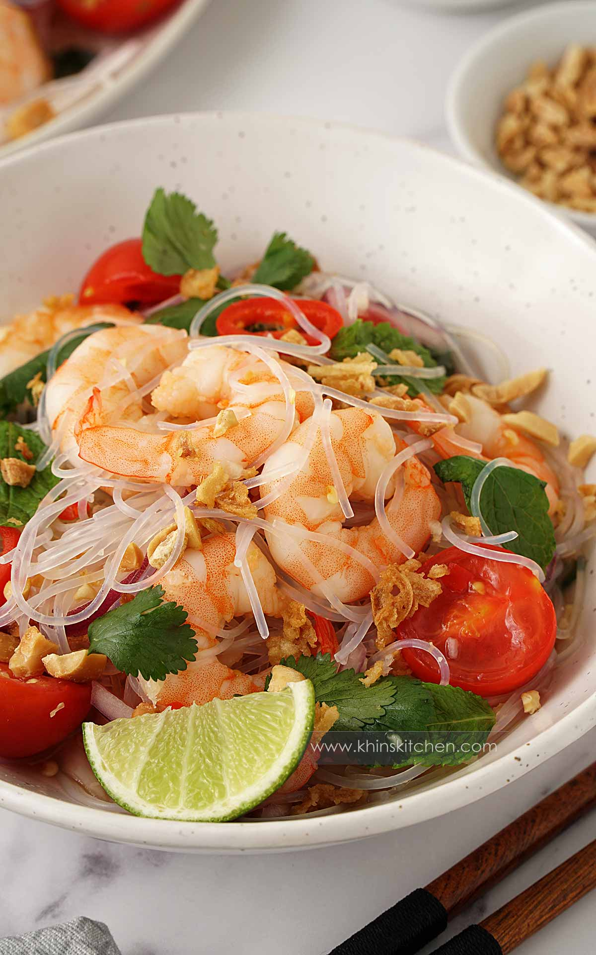 A white bowl containing prawns and glass noodle salad with cherry tomatoes and one lime wedge on the side.