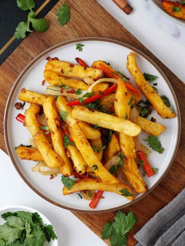 A white plate containing chip and stir fried bell pepper with crushed chilli topped with coriander.
