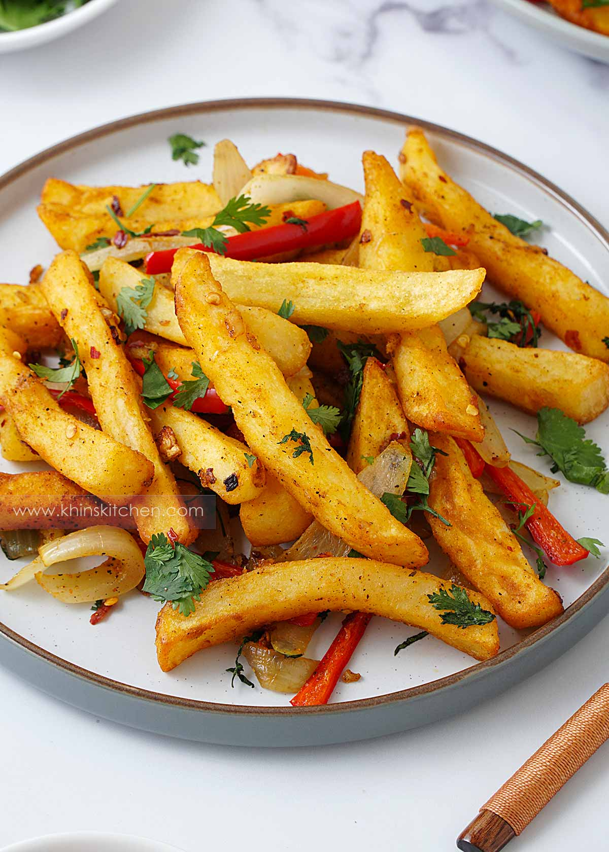 A white plate containing crispy fried chips and stir fried bell pepper with crushed chilli topped with coriander.